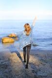 A menina encantador anda ao longo da costa e engana alegremente ao redor na areia Imagens de Stock Royalty Free