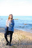 A menina encantador anda ao longo da costa e engana alegremente ao redor na areia Imagens de Stock
