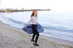A menina encantador anda ao longo da costa e engana alegremente ao redor na areia Fotografia de Stock
