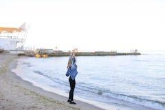 A menina encantador anda ao longo da costa e engana alegremente ao redor na areia Foto de Stock Royalty Free