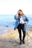 A menina encantador anda ao longo da costa e engana alegremente ao redor na areia Fotos de Stock Royalty Free