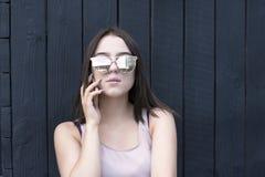 Menina encantador com dispositivo na moda que aprecia a conversação imagem de stock