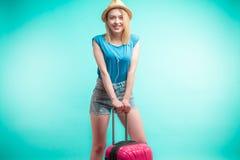 A menina encantador está inclinando-se na bagagem cor-de-rosa imagem de stock
