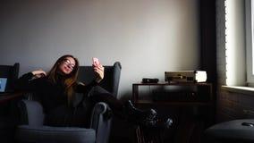 A menina encantador faz o selfie na câmera do ` s do smartphone e senta-se na cadeira no caf à moda na tarde na frente da janela video estoque