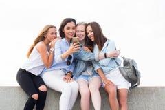 Menina encantador feliz do estudante que usa o smartphone e sorrindo no parque imagens de stock royalty free