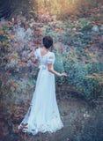A menina encantador inocente em um vestido caro do vintage branco longo obtém perdida na floresta, perdeu sua maneira, cores fres fotografia de stock royalty free