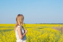 Menina encantador, louro com um ramalhete das flores em suas mãos imagem de stock royalty free