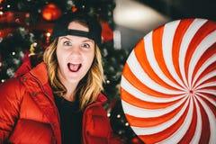 Menina encantador na moda no revestimento vermelho que veste o tampão à moda com pirulito gigantesco fotos de stock