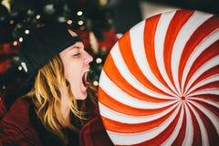 Menina encantador na moda no revestimento vermelho que veste o tampão à moda que morde o pirulito gigantesco imagens de stock