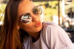 A menina encantador nos óculos de sol dá um beijo do ar fotos de stock royalty free