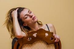 A menina encantador nova com cabelo longo senta-se em uma cadeira de madeira clássica do vintage isolada em um fundo claro Imagem de Stock Royalty Free