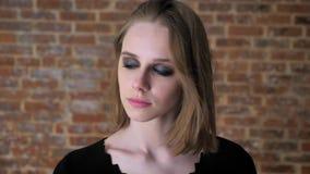 A menina encantador nova com olhos fumarentos está agitando a cabeça, jogando o cabelo, conceito de pensamento, fundo do tijolo vídeos de arquivo
