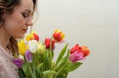 Menina encantador nova com um ramalhete das flores - tulipas multi-coloridas Fotos de Stock