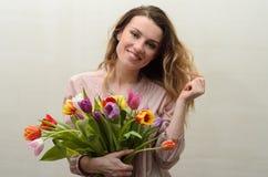 Menina encantador nova com um ramalhete das flores - tulipas multi-coloridas Imagens de Stock Royalty Free