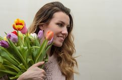 Menina encantador nova com um ramalhete das flores - tulipas multi-coloridas Imagens de Stock