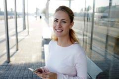 Menina encantador nova do moderno com o sorriso bonito que guardam o telefone esperto e o sorriso à câmera ao esperar um ônibus n Fotografia de Stock Royalty Free