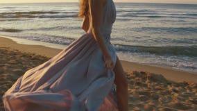 Menina encantador nova na luz longa - o vestido cor-de-rosa corre playfully ao longo do coastine no Sandy Beach com luzes dourada filme