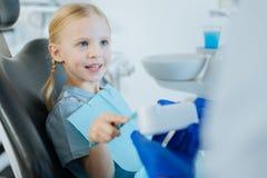 Menina encantador que aprende como escovar corretamente os dentes em dentistas imagens de stock