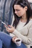 Menina encantador que guarda o close-up do telefone e da xícara de café foto de stock royalty free
