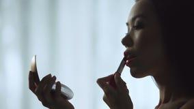 Menina encantador que põe com cuidado sobre o batom vermelho, bordos bonitos lentamente de pintura video estoque
