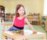 A menina encantador senta-se em uma tabela imagem de stock