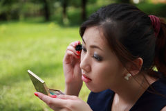 A menina encantadora olha no espelho de encontro ao parque verde Fotografia de Stock Royalty Free