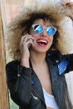 Menina encaracolado adulta nova que fala no telefone celular imagens de stock royalty free