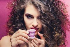 Menina encaracolado bonita com bebida colorida do tratamento de mãos de um copo roxo muito pequeno fotos de stock royalty free