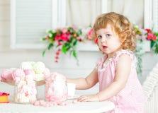Menina encaracolado bonito pequena em um vestido cor-de-rosa com laço e às bolinhas que sentam-se na tabela e que comem doces dif Fotos de Stock Royalty Free