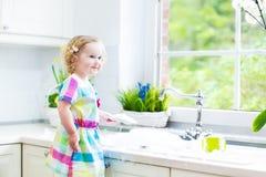 Menina encaracolado da criança em pratos de lavagem do vestido colorido foto de stock royalty free