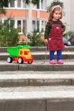 Menina encaracolado do bebê de um ano que puxa um caminhão que tenta superar um obstáculo das etapas Imagens de Stock Royalty Free
