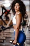 A menina encaracolado do escuro-cabelo de Atletic vestida em um sportswear est? estando com os pesos em suas m?os no gym moderno fotos de stock royalty free