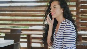 A menina encaracolado encantador está falando no telefone filme