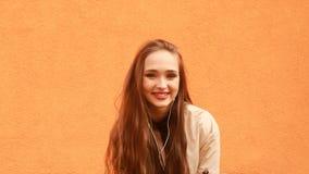 Menina encaracolado engraçada do moderno nos fones de ouvido que sorri, beijando no fundo alaranjado video estoque