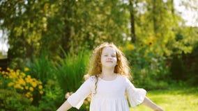 A menina encaracolado está descansando, fazendo os exercícios, bocejando no parque do verão vídeos de arquivo