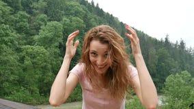 A menina encaracolado feliz nas montanhas aprecia a chuva do verão sem um guarda-chuva A menina é feliz e risos alegremente vídeos de arquivo
