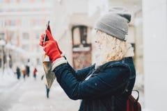 Menina encaracolado loura nova que faz a foto no smartphone Fotos de Stock Royalty Free