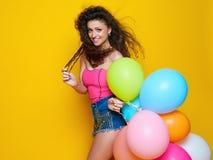 Menina encaracolado nova e bonita em uma camisa cor-de-rosa e short azul em um fundo amarelo que guarda balões coloridos e riso Fotografia de Stock