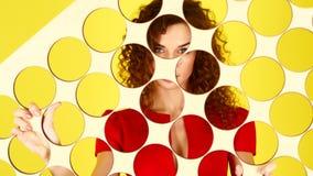Menina encaracolado nova em um vestido vermelho em um fundo amarelo Vista na c?mera atrav?s da tela 4K video estoque