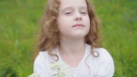 A menina encaracolado pequena dá um ramalhete para serir de mãe ou genar filme