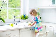 Menina encaracolado pequena da criança em pratos de lavagem do vestido colorido imagens de stock royalty free