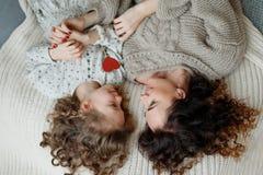 A menina encaracolado pequena e sua mãe encontram-se junto na cama, olhares em se com grande amor, apreciam a unidade Vista de fotografia de stock