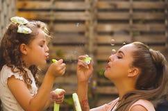 Menina encaracolado pequena feliz que joga com bolhas de sabão em uma natureza do verão com sua mamã, em um fundo borrado Fotografia de Stock