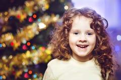 Menina encaracolado pequena perto da árvore de Natal imagem de stock