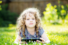 Menina encaracolado pequena que encontra-se na grama e realizar na tabuleta das mãos Fotos de Stock Royalty Free