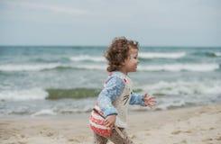 Menina encaracolado pequena que joga na areia no litoral Imagem de Stock