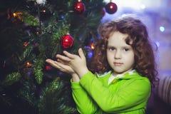 Menina encaracolado perto da árvore de Natal fotos de stock royalty free