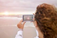 Menina encaracolado que fotografa o nascer do sol no oceano fotos de stock