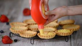 A menina enche tartlets com o creme pastry Sobremesa doce dos tartlets video estoque