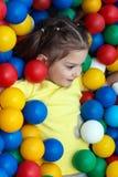 A menina encontra-se em bolas coloridas fotos de stock royalty free